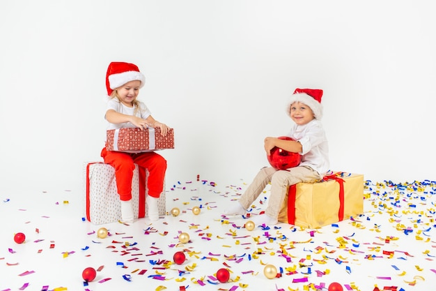 Twee grappige kleine kinderen in kerstmuts zittend op geschenkdozen. geïsoleerd op witte achtergrond, confetti op een vloer. kerstmis en nieuwjaar concept.