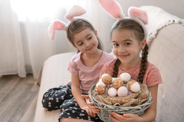 Twee grappige kleine meisjes in konijnenoren thuis op de bank met een mand met paaseieren