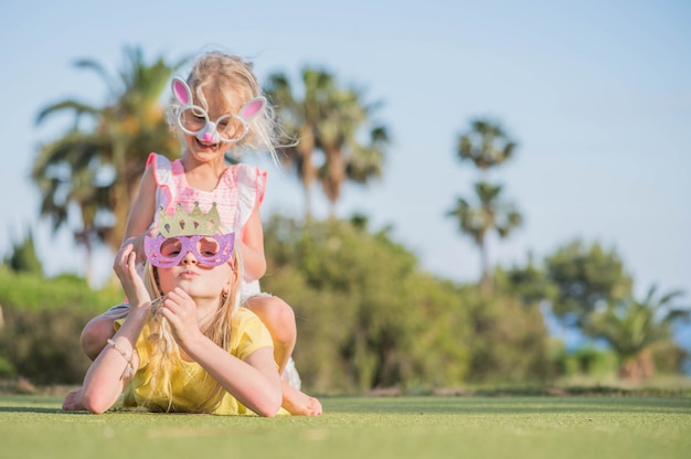 Twee grappige kleine meisjes met papieren masker. kinderverjaardag, zomerpret.