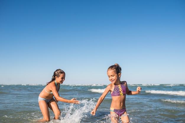 Twee grappige kleine meisjes springen in de luidruchtige zeegolven en genieten van de langverwachte vakantie op een zonnige warme zomerdag. concept zee vakantie en reizen met kinderen