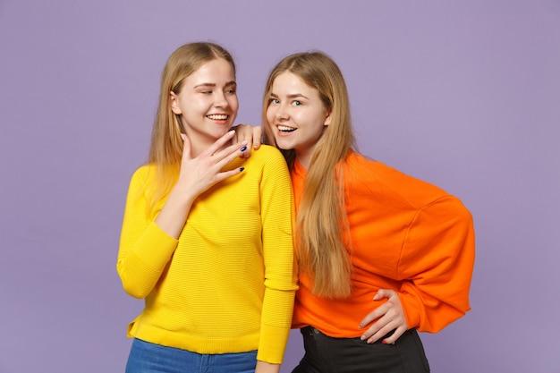 Twee grappige lachende jonge blonde tweeling zusters meisjes in levendige kleurrijke kleding staan, geïsoleerd op pastel violet blauwe muur. mensen familie levensstijl concept.