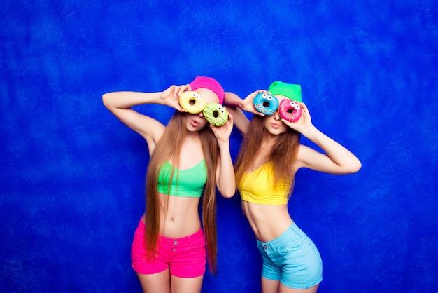Twee grappige meisjes die donuts tegen de ogen houden en glimlachen