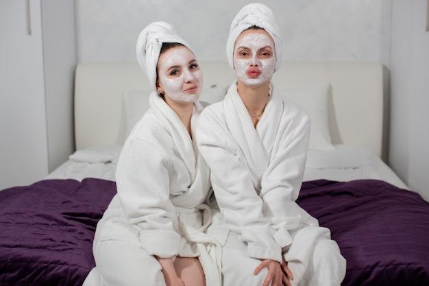 Twee grappige meisjes in gewaden, een handdoek op hun hoofd en een gezichtsmasker zittend op het bed, rechtstreeks in de camera starende foto van hoge kwaliteit