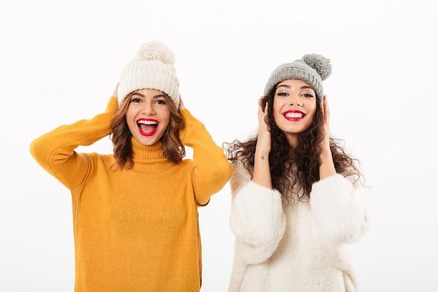 Twee grappige meisjes in sweaters en hoeden die pret samen over witte muur hebben