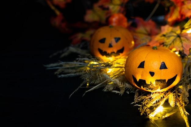 Twee grappige of boze pompoenen jack lantern hoofd in het hooi, herfst gele bladeren