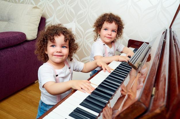 Twee grappige tweelingzusjes die samen piano spelen lachende lachende kinderen leren piano spelen het concept van het opleiden van kinderen