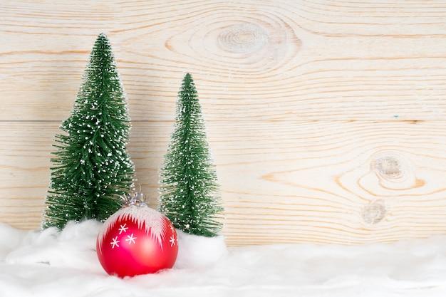 Twee groenblijvende sparren en rode bal, besneeuwde kerstmissamenstelling, houten achtergrond