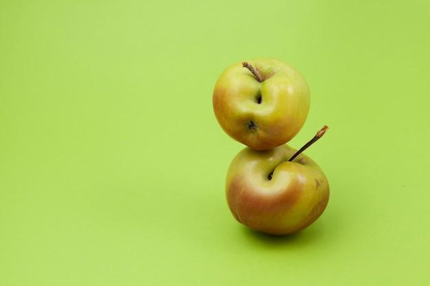 Twee groene appels met gebreken op lichtgroen