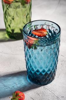 Twee groene en blauwe geometrische glazen beker met zoet water en aardbeien fruit met kleurrijke schaduw lichtstralen op stenen betonnen oppervlak