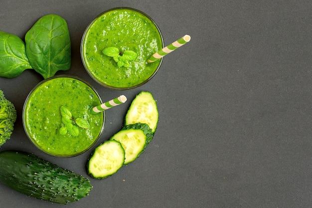 Twee groene smoothies met ingrediënten op donker. bovenaanzicht.