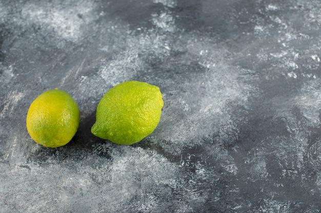 Twee groene verse citroenen op een marmeren ondergrond.