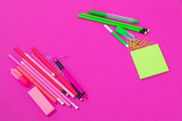Twee groepen roze en felgroene kantoorapparatuur liggen aan weerszijden op roze oppervlak geïsoleerd