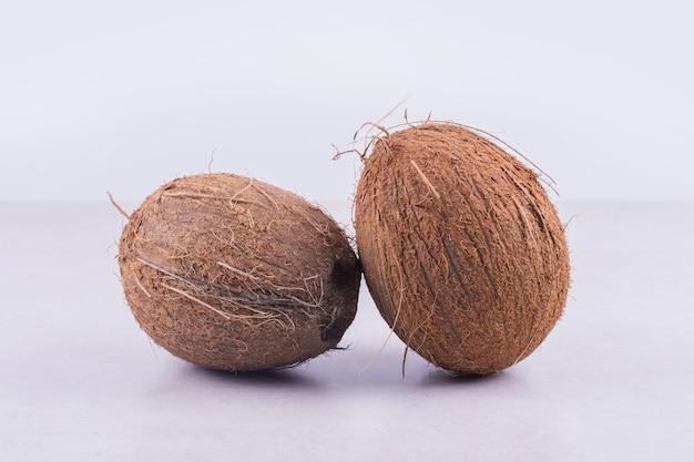 Twee grote, bruine kokosnoten op wit