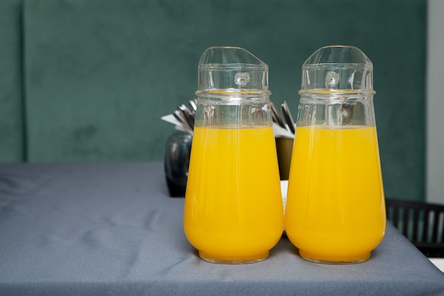 Twee grote doorzichtige kannen met fruitdrank. jus d'orange op grijze lijst.