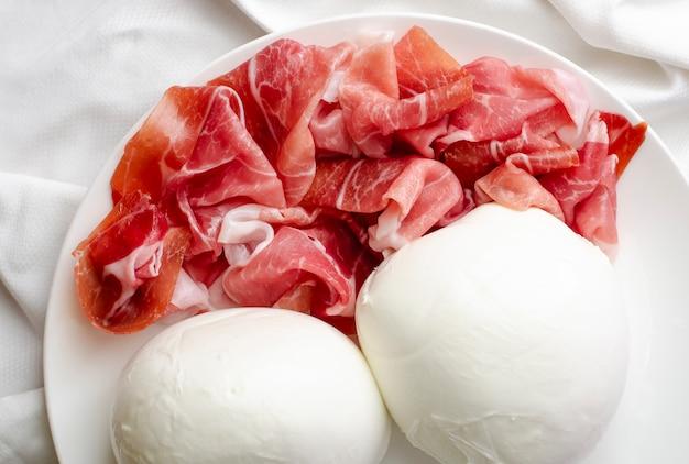 Twee grote mozzarellaballen en prosciutto crudoon een witte plaat