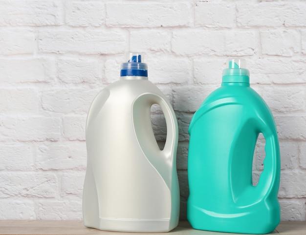 Twee grote plastic flessen met vloeibaar wasmiddel op witte bakstenen muur