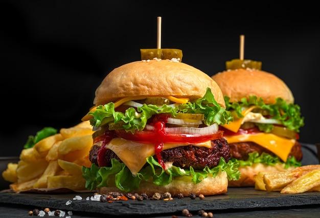 Twee grote, sappige hamburgers met rundvlees, kaas, groenten en frietjes op een zwarte achtergrond. zijaanzicht, close-up.