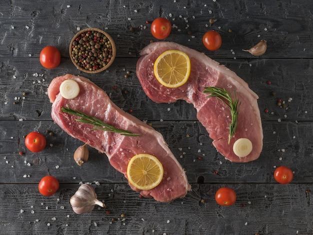 Twee grote varkenssteaks met citroen, tomaten, kruiden en knoflook op een houten tafel. ingrediënten voor het koken van vleesgerechten. het uitzicht vanaf de top.