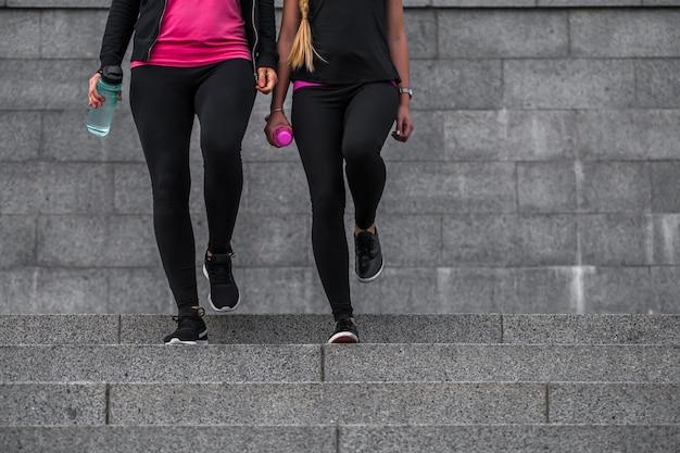 Twee gymmeisjes in mooie sportkleren komen de trap op, het concept van fitness en sport gezonde levensstijl