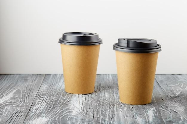 Twee halen papieren koffiekopjes op grijze houten achtergrond weg