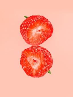 Twee halve beetje aardbeien die op rode pastelkleur worden geïsoleerd.