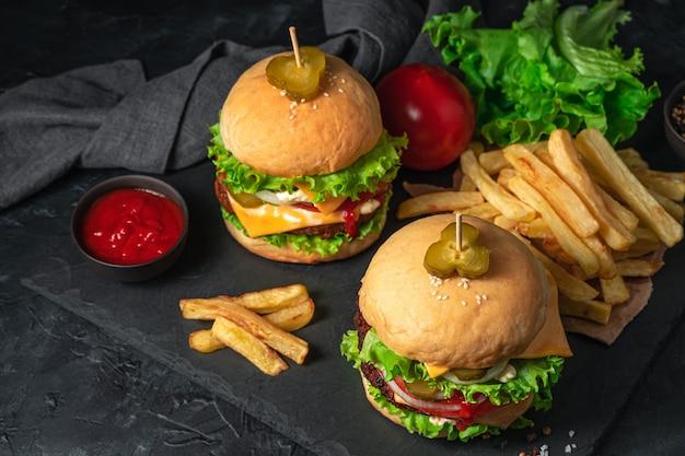 Twee hamburgers, frietjes en jus op een zwarte achtergrond. fast food. horizontale weergave, kopieer ruimte.