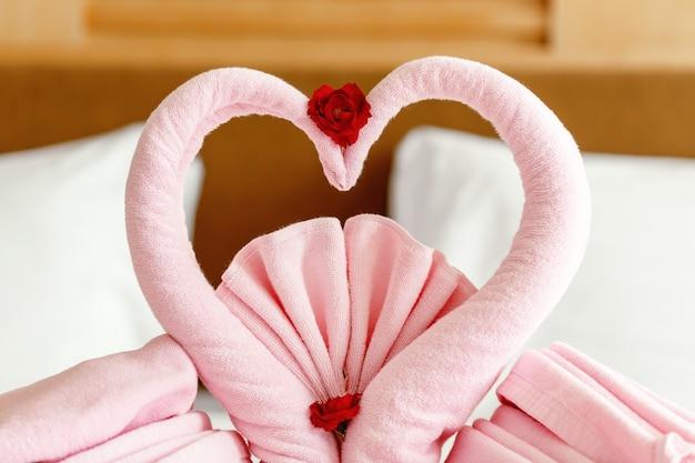 Twee handdoekzwanen gevormd op het bed in huwelijksceremonie