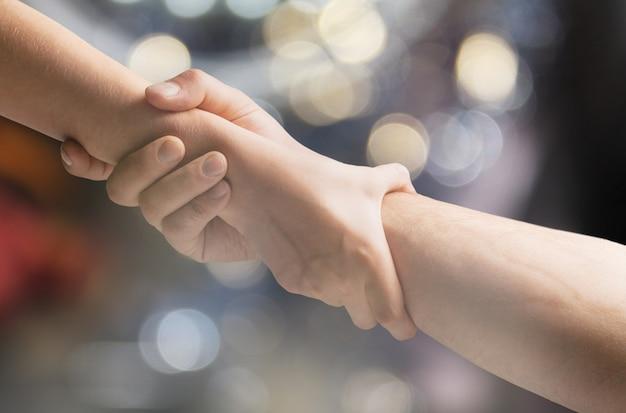 Twee handen die een ander helpen