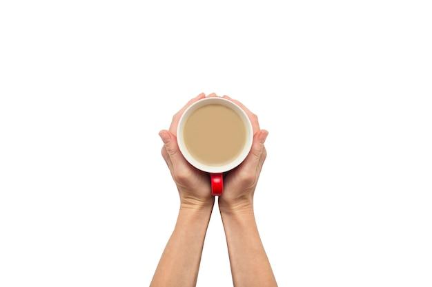 Twee handen die een kop met hete koffie op wit geïsoleerde achtergrond houden. ontbijtconcept met koffie of thee. goedemorgen, nacht, slapeloosheid. plat lag, bovenaanzicht