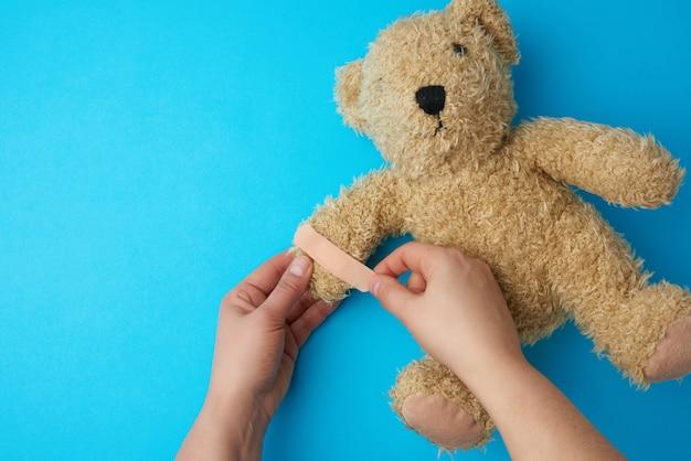 Twee handen die een teddybeer en het lijmen van een pleister op een poot