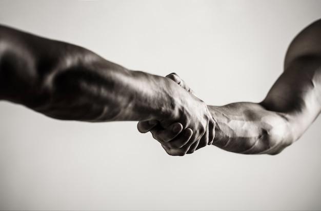 Twee handen, geïsoleerde arm, helpende hand van een vriend. handdruk, wapens. vriendelijke handdruk, vrienden begroeten. teamwerk en vriendschap. detailopname. redding, helpend gebaar of handen. concept van redding.