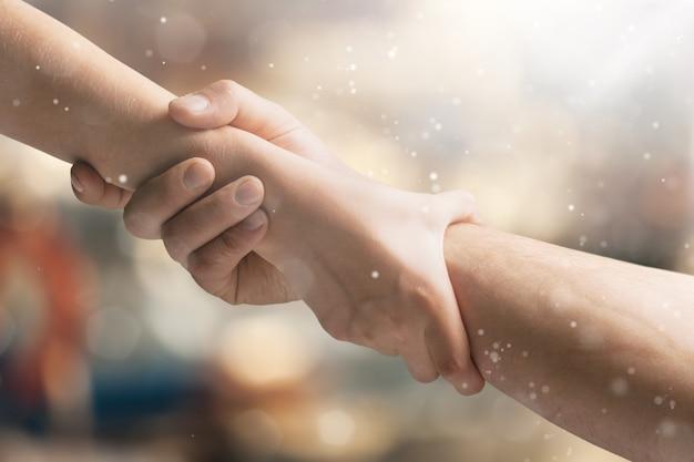 Twee handen helpen een ander op onscherpe achtergrond