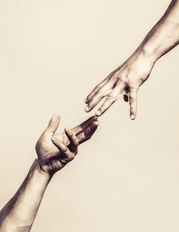 Twee handen, helpende arm van een vriend, teamwork. helpende hand uitgestrekte, geïsoleerde arm, redding. sluit omhoog hulphand. helpende hand concept en internationale dag van vrede, ondersteuning. zwart en wit.