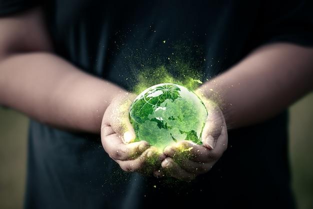 Twee handen houden de groene bol en het magische licht vast. concept van het redden van de wereld en de dag van de aarde