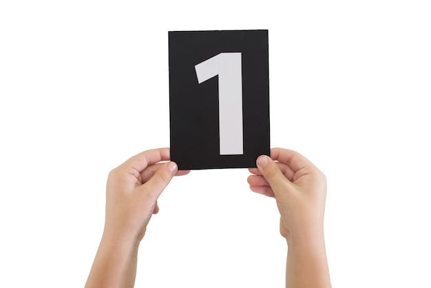 Twee handen houden een zwarte papieren kaart met nummer 1 geïsoleerd op een witte achtergrond.
