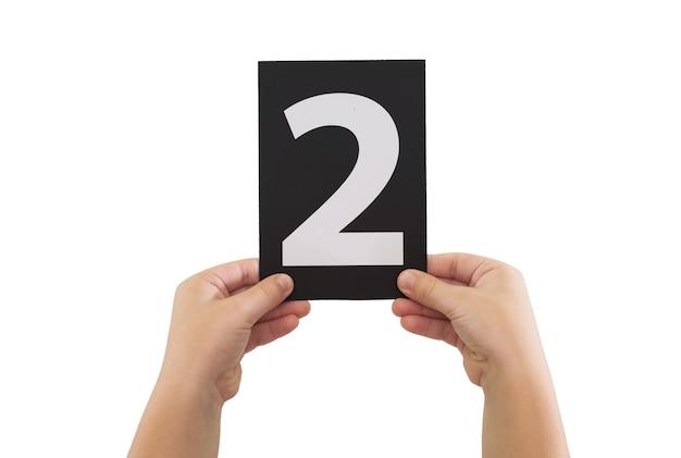 Twee handen houden een zwarte papieren kaart met nummer 2 geïsoleerd op een witte achtergrond.
