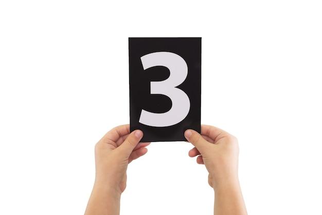Twee handen houden een zwarte papieren kaart met nummer 3 geïsoleerd op een witte achtergrond.