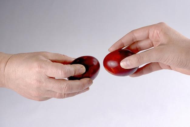 Twee handen houden eieren vast en proberen elkaars ei te breken
