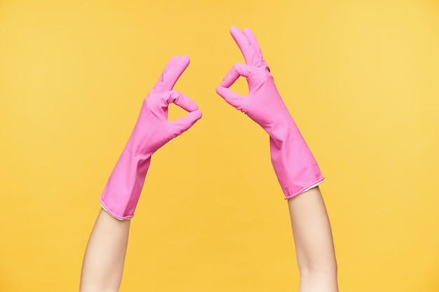 Twee handen in rubberen handschoenen positieve emoties uiten en goed gedaan gebaar vormen met opgeheven vingers, geïsoleerd op oranje achtergrond. menselijke handen en gebaren concept