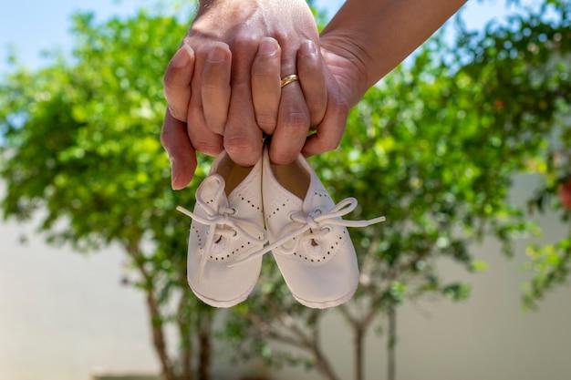 Twee handen met babyschoenen. zwangerschapsconcept.