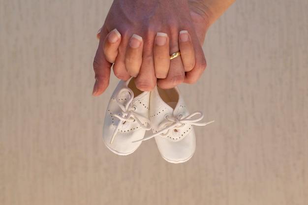 Twee handen met babyslofjes. zwangerschap concept.