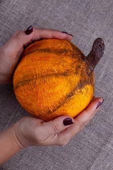 Twee handen met een bruine manicure houden een zelfgemaakte oranje pompoen van papier-maché voor halloween op een horizontaal jute-oppervlak