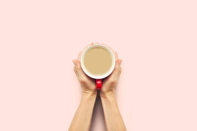 Twee handen met een kopje warme koffie op een roze achtergrond. ontbijtconcept met koffie of thee. goedemorgen, nacht, slapeloosheid. plat lag, bovenaanzicht