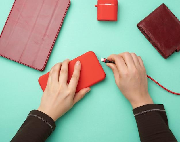 Twee handen met een rode mobiele smartphone en een oplaadkabel op een groene achtergrond
