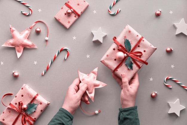 Twee handen met een speelgoedster en een ingepakt kerstcadeau