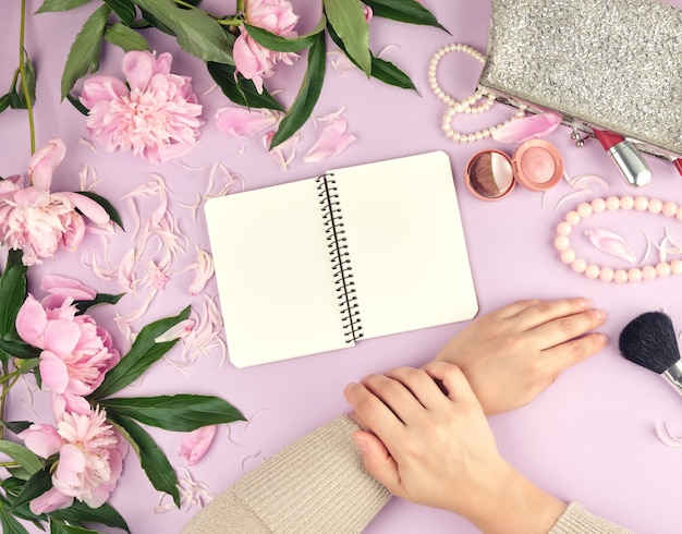 Twee handen met een zachte huid van een jong meisje en een handtas met cosmetica, boeket van bloeiende roze pioenrozen
