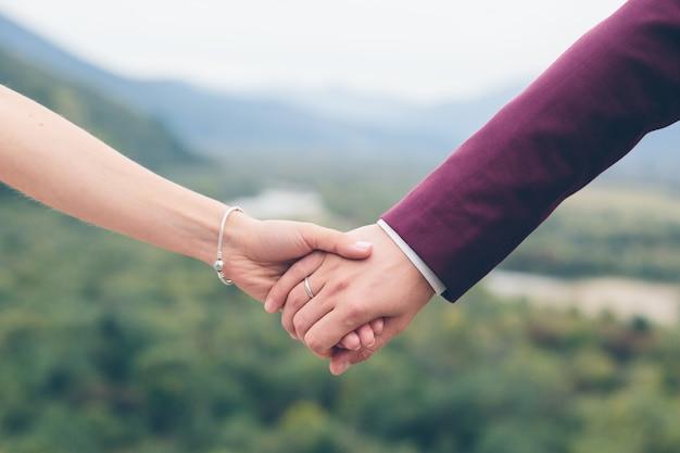 Twee handen met elkaar, trouwfoto, bruid en bruidegom op een achtergrond van bergen
