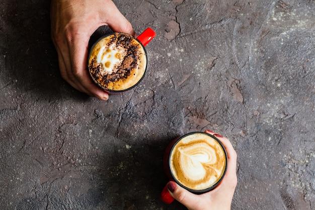 Twee handen met kopjes warme koffie op een donkere achtergrond, bovenaanzicht