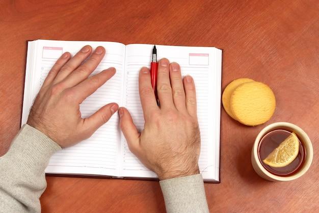 Twee handen met rode pen die op een notitieboekje op bureau met thee en koekjes liggen