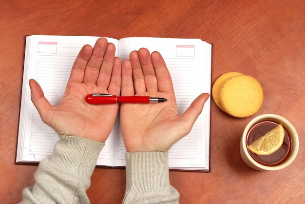Twee handen met rode pen liggend op een notitieboekje op bureau met thee en koekjes biscuit